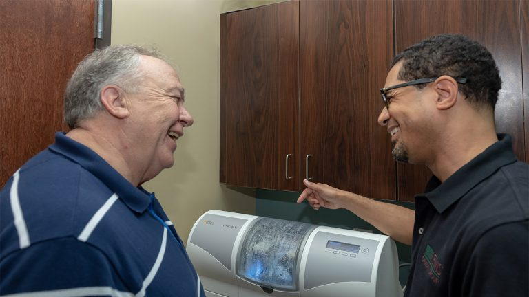 Patient and Dr. Lewis pointing at CEREC Same Day Crowns machine